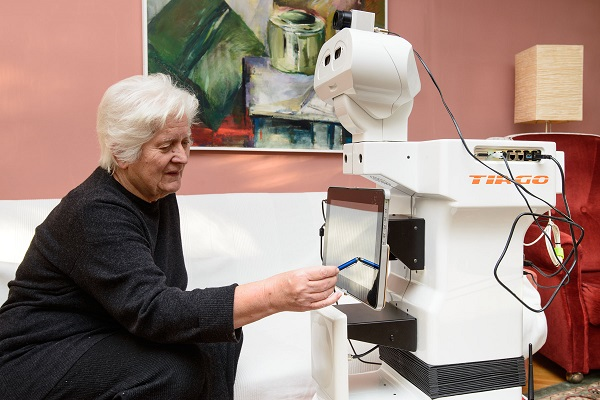An Image Dpicting The Concept Of Cobots Helping Elders - An Old Lady Operating Collaborative Robot From Her Home.