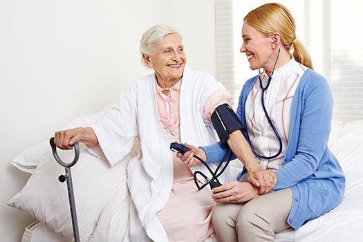 Senior Woman With Nurse During Stroke Recovery Session.