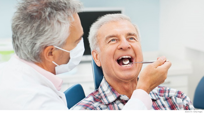 An image representing a dentist doing dental treatment of senior male patient.