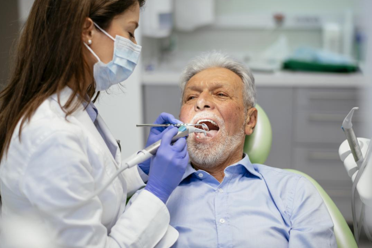 An Image Representing Senior man taking dental treatment in a leading dental clinic.